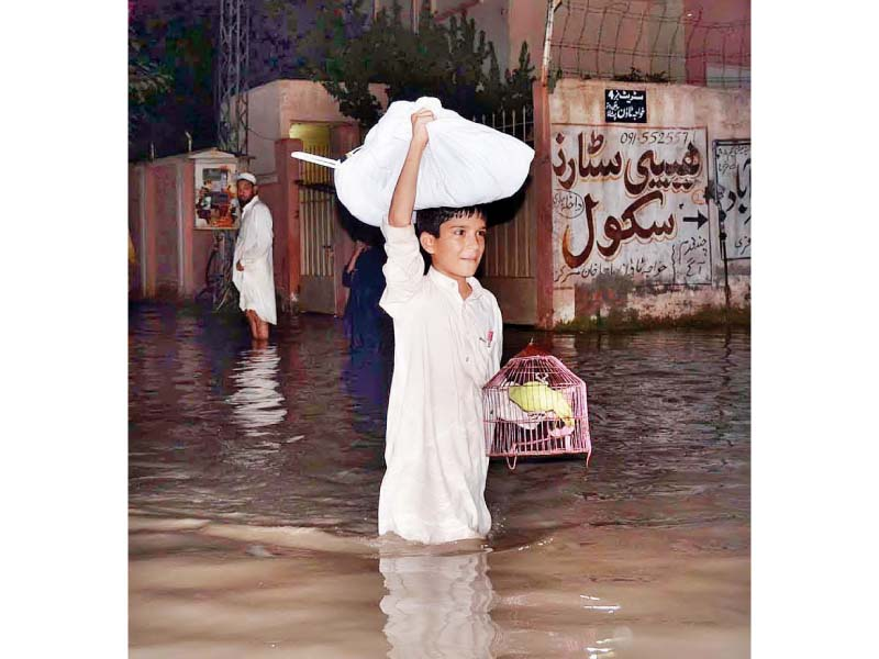a youngster shifts his valuables to a safer place as floodwater enters budhani area near peshawar photo app