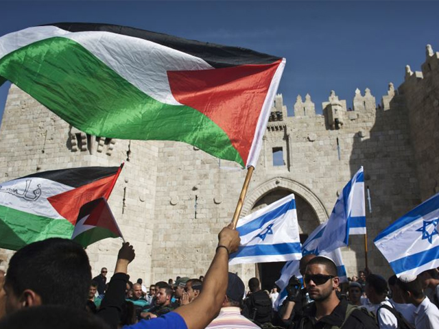 Palestinian protesters wave Palestinian flags as Israelis carrying Israeli flags walk past in front of the Damascus Gate outside Jerusalem's Old City. PHOTO: REUTERS