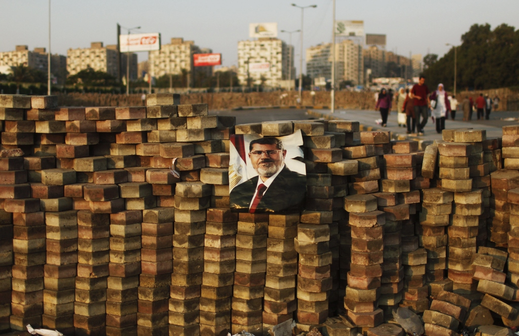 supporters of deposed egyptian president mohamed mursi depicted in poster walk behind a makeshift barrier built to demarcate their sit in area around raba 039 al adawya mosque east of cairo august 3 2013 photo reuters