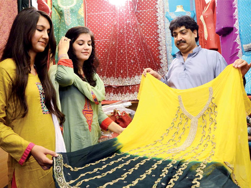 girls check out embroidered dresses at moti bazar as eid shopping catches momentum photo online