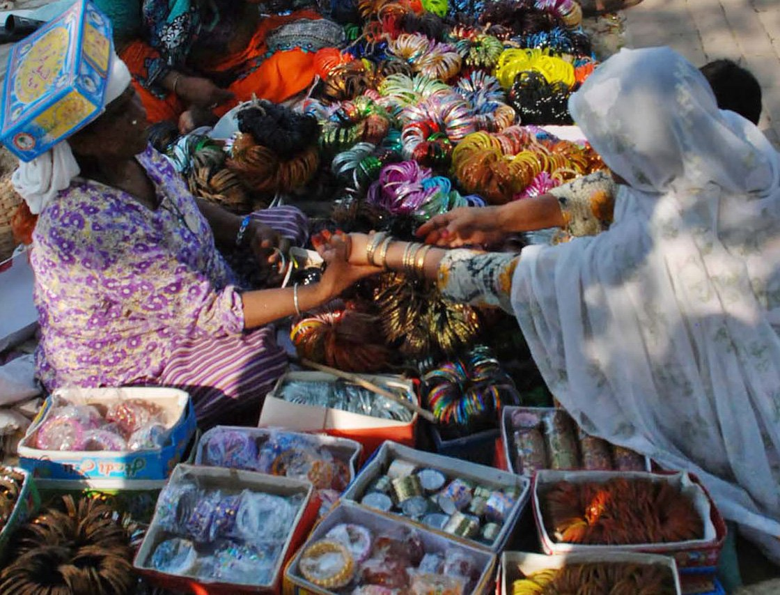 a woman selling bangles at her set up in sunday bazar photo inp