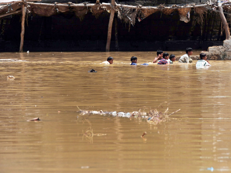 youth swim in floodwaters on monday following heavy monsoon rains in karachi photo afp