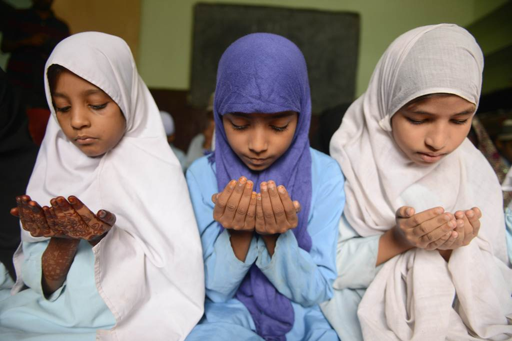 Indian Muslim students offer 'Dua' prayers in their class room during the holy month of Ramadan at Madrasatur-Rashaad religious school in Hyderabad on July 17, 2013. PHOTO: AFP.