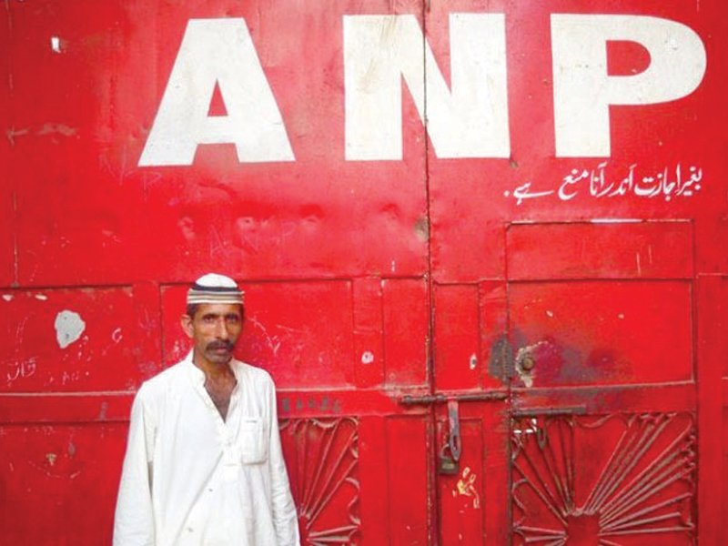 a supporter of the awami national party stands outside the closed doors of the party s office in sohrab goth karachi the party decided to keep their offices shut following a string of attacks on its offices during the elections photo file