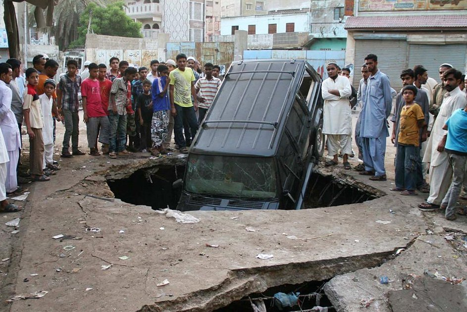 people standing near the car that was destroyed in the blast near football ground in lyari photo online