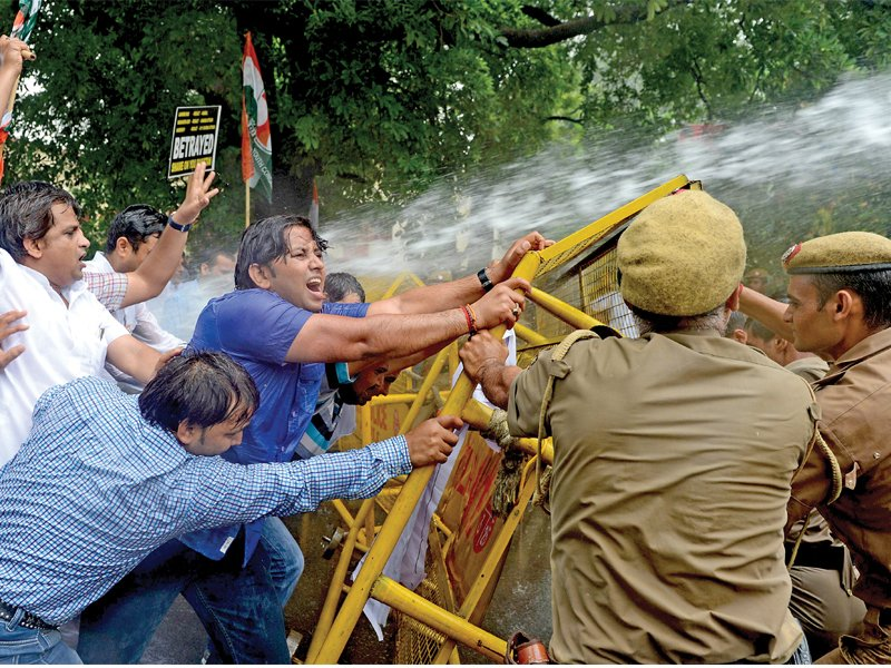 a stream of water from a police water cannon covers indian youth congress activists as they stage a violent protest near the pakistan high commission in new delhi photo afp