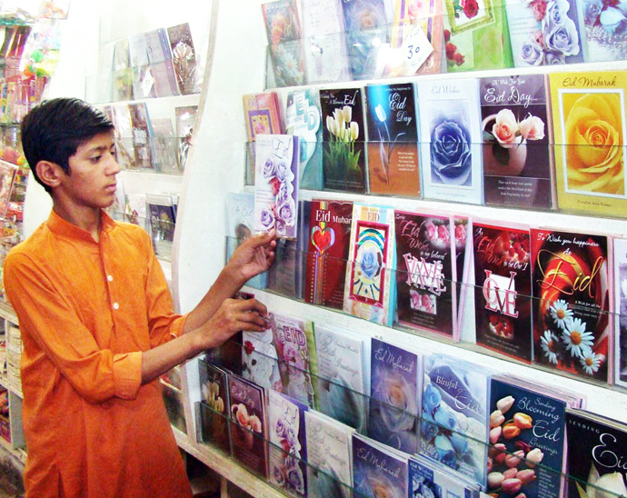 a young man selecting eid cards in pakistan photo app file
