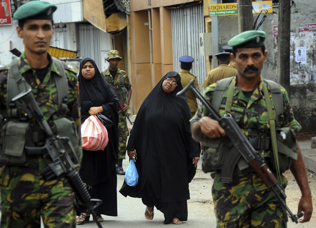 two muslim women walk behind patrolling special task force commandos outside a vandalized mosque in colombo photo reuters
