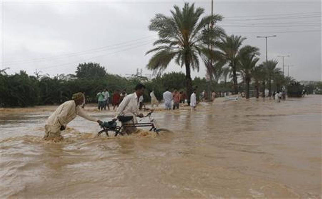 men push their bicycles through flood waters on the outskirts of karachi august 4 2013 photo reuters