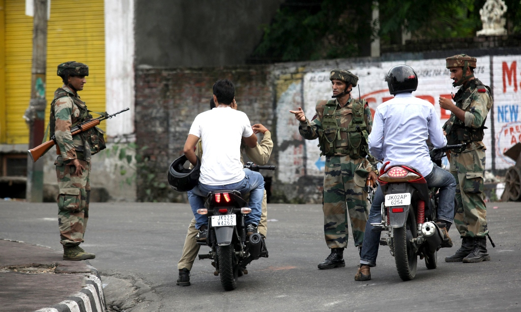 indian army soldiers speak with motorcyclists during a curfew in jammu on august 11 2013 photo afp