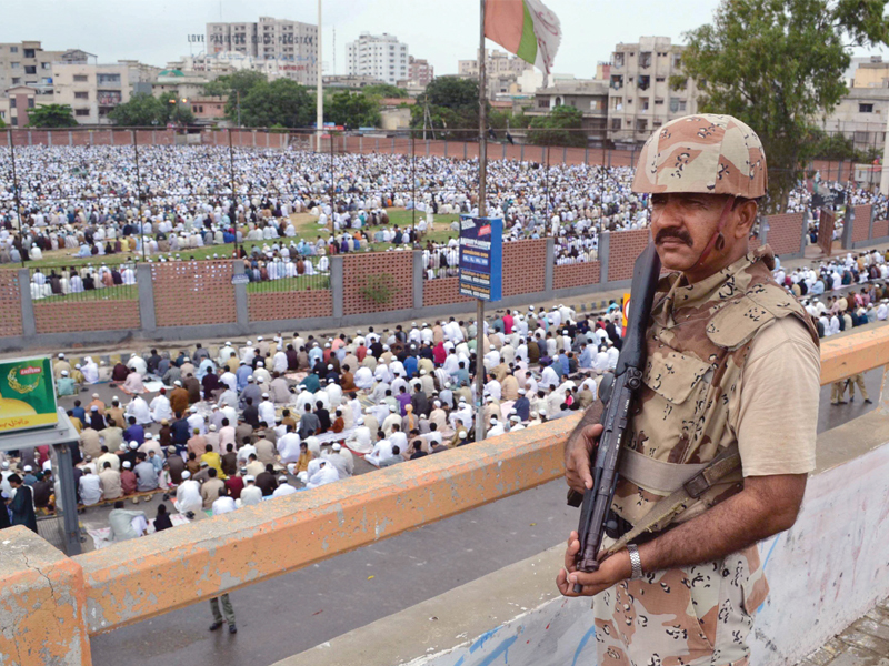 a rangers official stands guard at the eid prayers being held at the eidgah ground in nazimabad over the three days at least 22 people were killed in the city police officials said that the security in the city was heightened to pre empt terrorist activities photo rashid ajmeri express