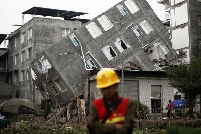 a rescuer walks in front of a damaged building after the earthquake in april in lingguan town of baoxing county sichuan province photo reuters