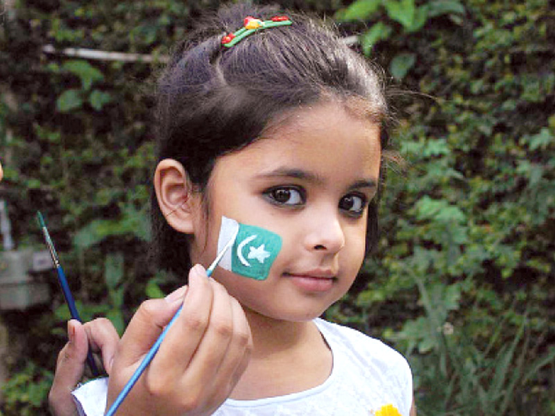 a young girl gets a flag painted on her cheek photo waseem imran express online