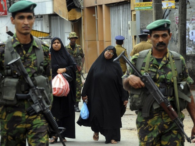 Two Muslim women walk behind patrolling Special Task Force Commandos outside the mosque that was vandalised. PHOTO: REUTERS