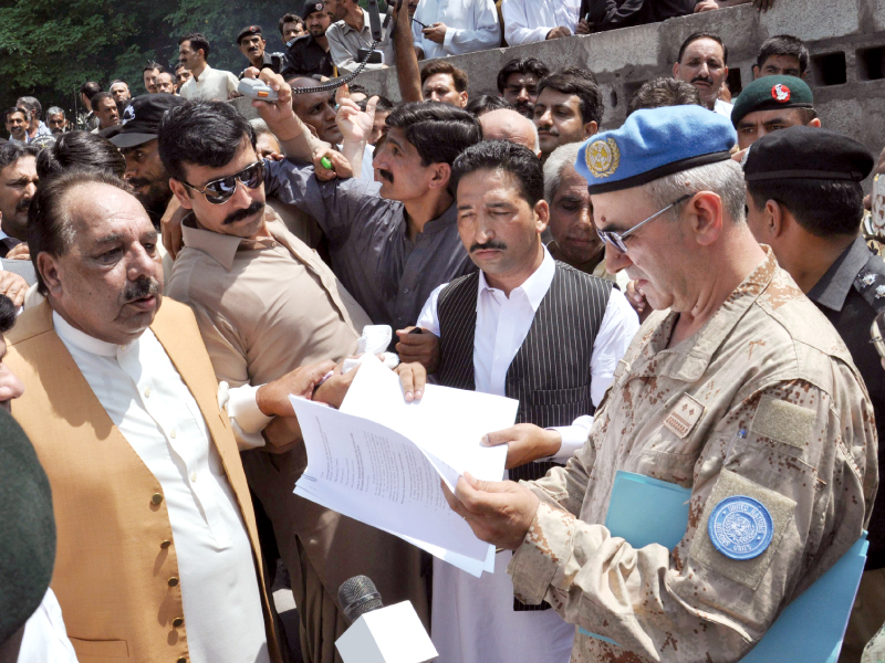 azad jammu and kashmir s prime minister chaudhry abdul majeed hands a memorandum to un officials in muzaffarabad photo afp