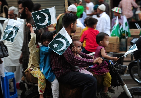 pakistani children carry national flags as they ride on a motorcycle ahead of the country 039 s independence day in karachi on august 12 2013 photo afp