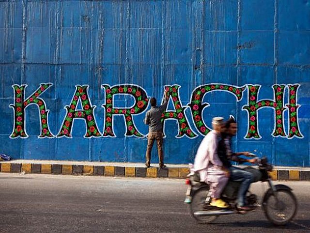 A street artist applies the final touches to a mural, part of the 'I am Karachi' campaign, as a motorcycle passes by in Karachi, Pakistan, on Friday, May 29, 2015. Pakistan's budget is scheduled to be presented on June 5. PHOTO: GETTY