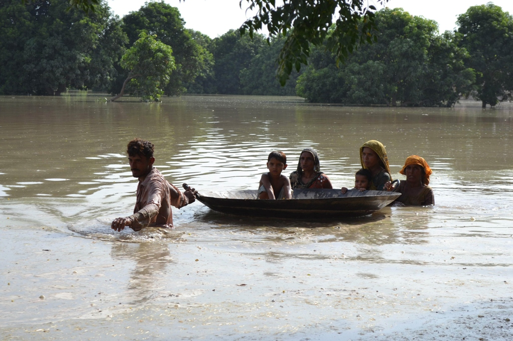 pakistani villagers wade through floodwaters on the outskirts of multan on august 21 2013 photo afp