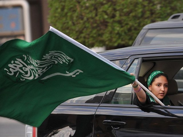 A Saudi girl waves a national flag during celebrations of the 81st Saudi Arabian National Day in the desert kingdoms capital Riyadh on September 23, 2011. PHOTO: AFP