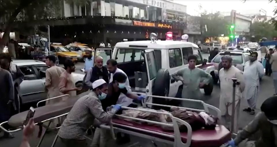 A screen grab shows people carrying an injured person to a hospital after an attack at Kabul airport, in Kabul, Afghanistan August 26, 2021. PHOTO: REUTERS