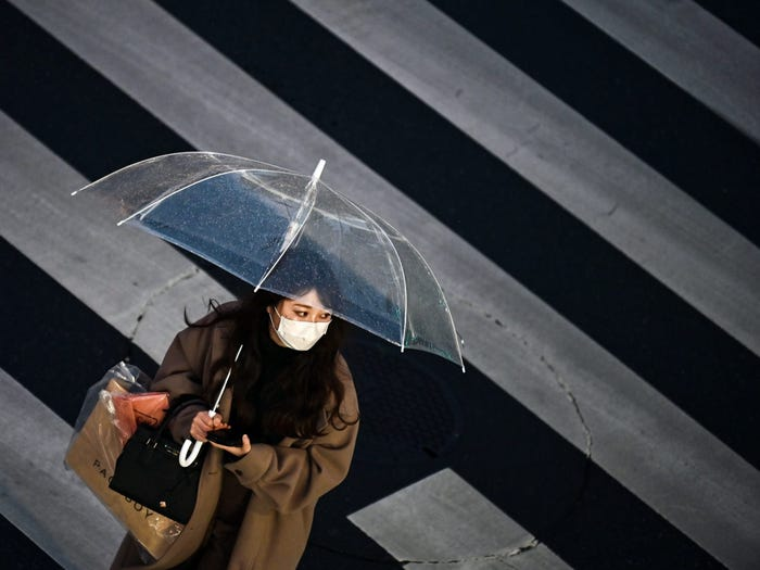 A woman crosses the street in Tokyo on January 28, 2021. CHARLY TRIBALLEAU/AFP