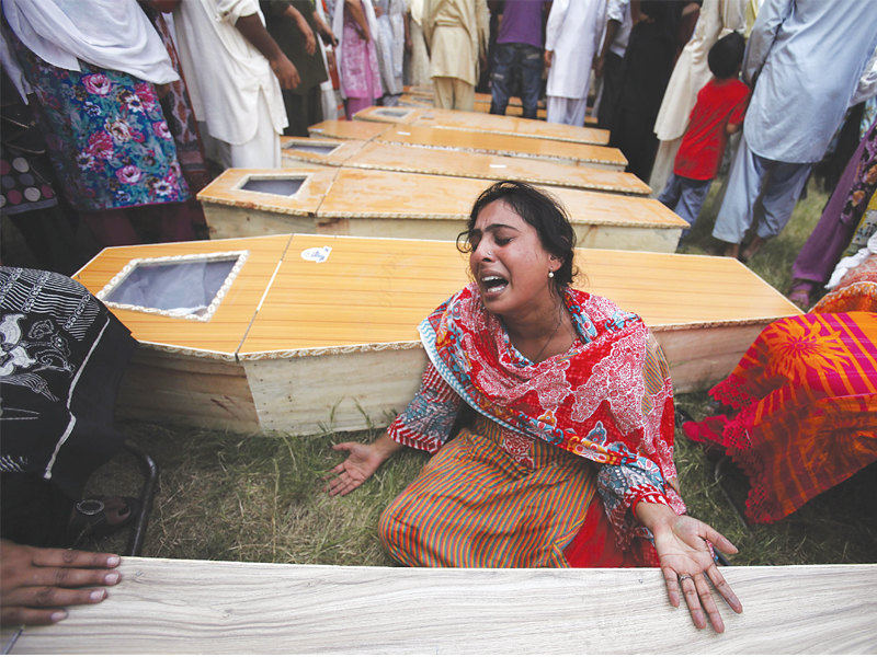 A woman mourns next to the casket of her brother, who was killed in the twin suicide attacks.  PHOTO: REUTERS