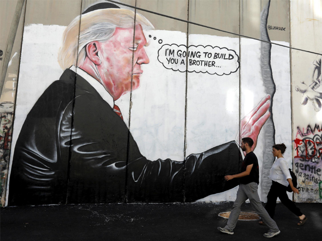 A mural resembling the work of elusive artist Banksy depicting President Donald Trump wearing a Jewish skullcap, is seen on Israel's West Bank separation barrier in the West Bank city of Bethlehem. PHOTO: AP