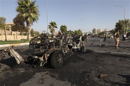 kurdish security forces inspect the site of a bomb attack in the city of arbil photo reuters