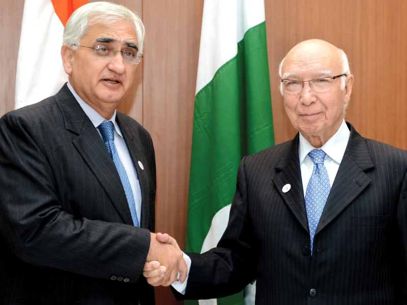 adviser to pm on foreign affairs sartaj aziz shakes hands with indian minister for external affairs salman khurshid during a meeting in new delhi photo afp