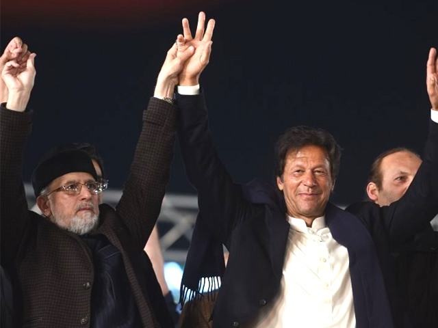 Canada based Pakistani cleric, Tahir-ul Qadri (L) of Pakistan Awami Tehreek (PAT) and Pakistani opposition leader and head of the Pakistan Tehreek-e-Insaf (PTI), Imran Khan, raise hands during an anti-government protest rally in Lahore on January 17, 2018. PHOTO: AFP