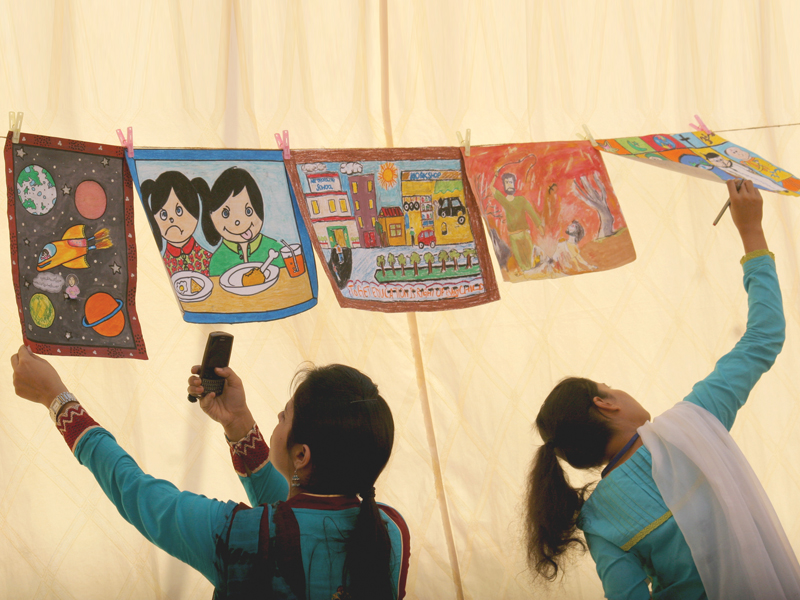 Schoolchildren look at the paintings of five shortlisted candidates of different schools at a programme hosted by NGO Aahung to celebrate Universal Children's Day on Wednesday. PHOTO: ATHAR KHAN/EXPRESS