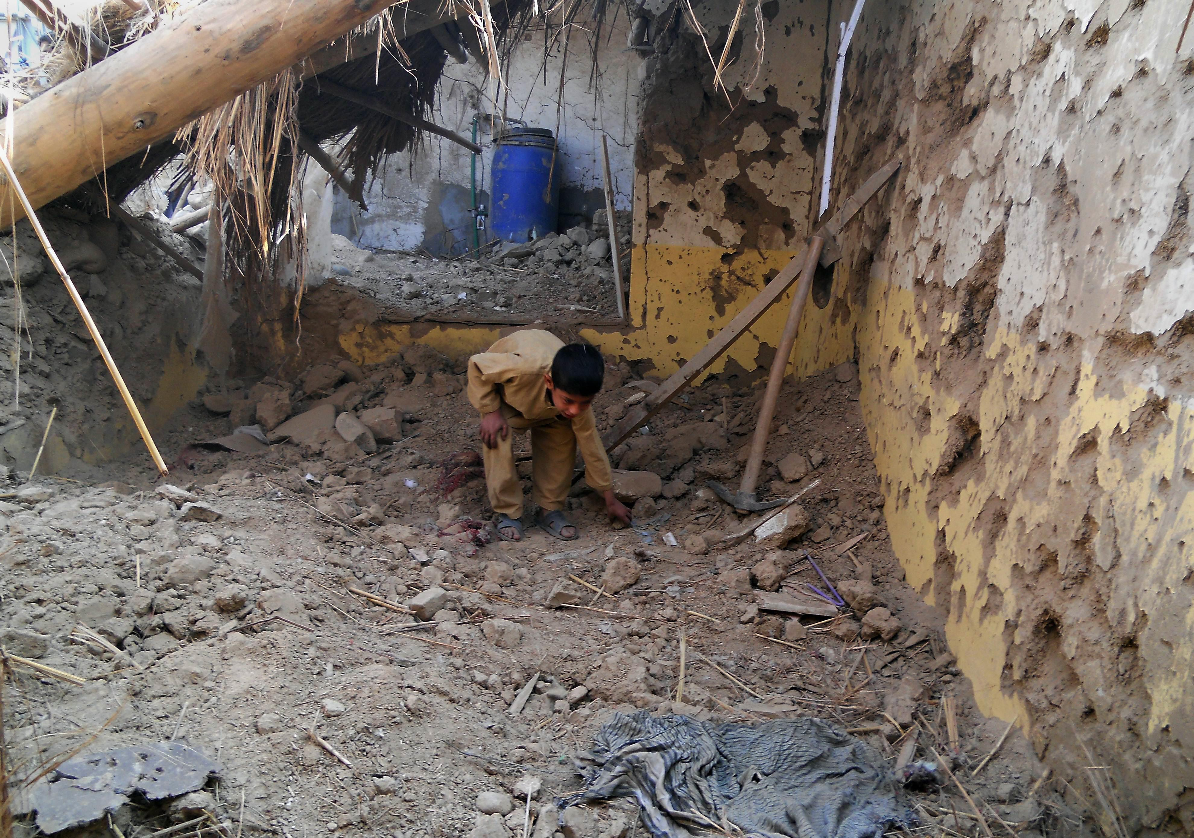 a child sifts through rubble at a destroyed seminary after a drone strike in hangu photo afp