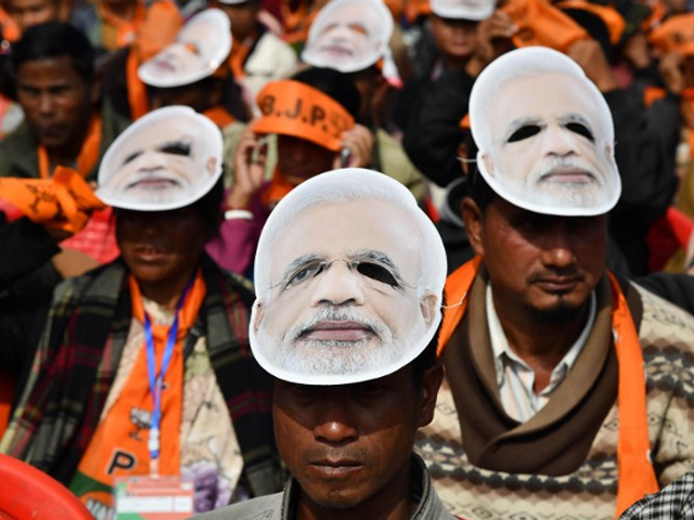 supporters of the bharatiya janata party bjp wearing masks of indian prime minister narendra modi listen to modi during a public rally in shillong on december 16 2017 photo afp