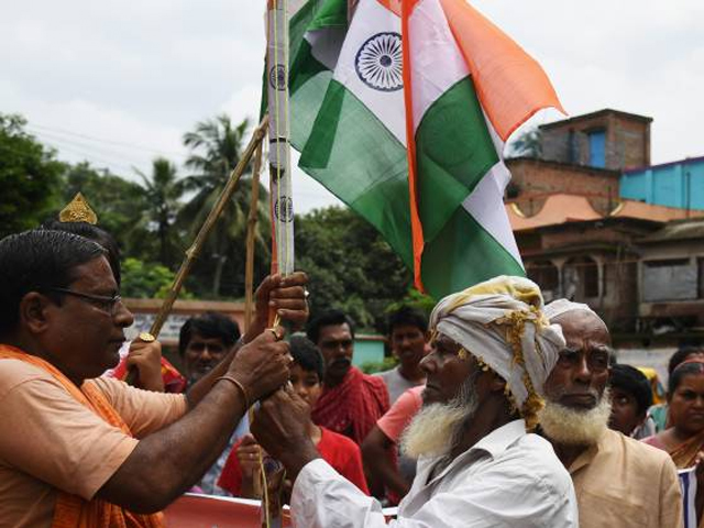 A Hindu priest (L) and Muslim mawlawi hoist the Indian national flag to celebrate Indian Independence Day in Majhdia village of Nadia district, east of Krishnanagar in West Bengal on the Bangladeshi border, on August 18, 2017. PHOTO: AFP