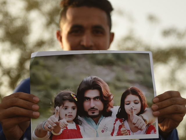 A protestor holds a photograph of Naqeebullah Mehsud. PHOTO: AFP