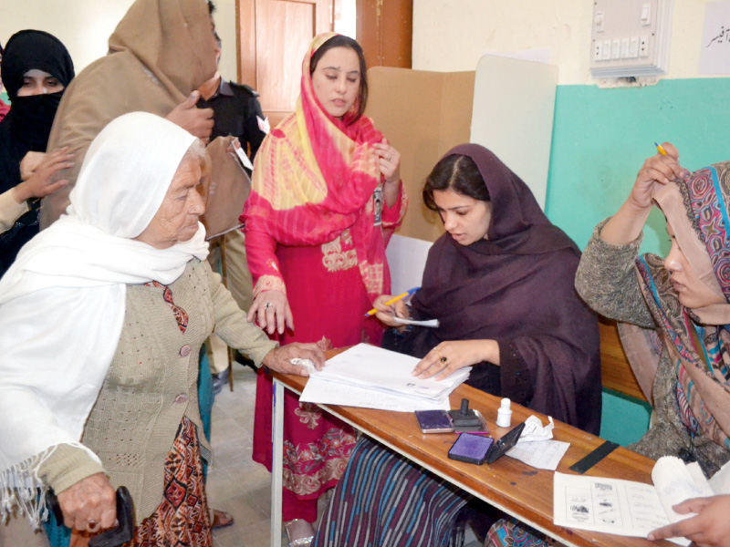 an elderly woman checks her name in the electoral list at a polling station in balochistan photo express naseem james