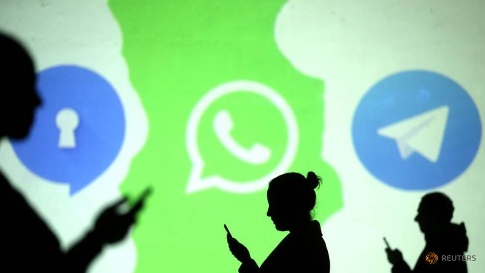 silhouettes of mobile users are seen next to logos of social media apps signal whatsapp and telegram projected on a screen in this picture illustration taken march 28 2018 photo reuters