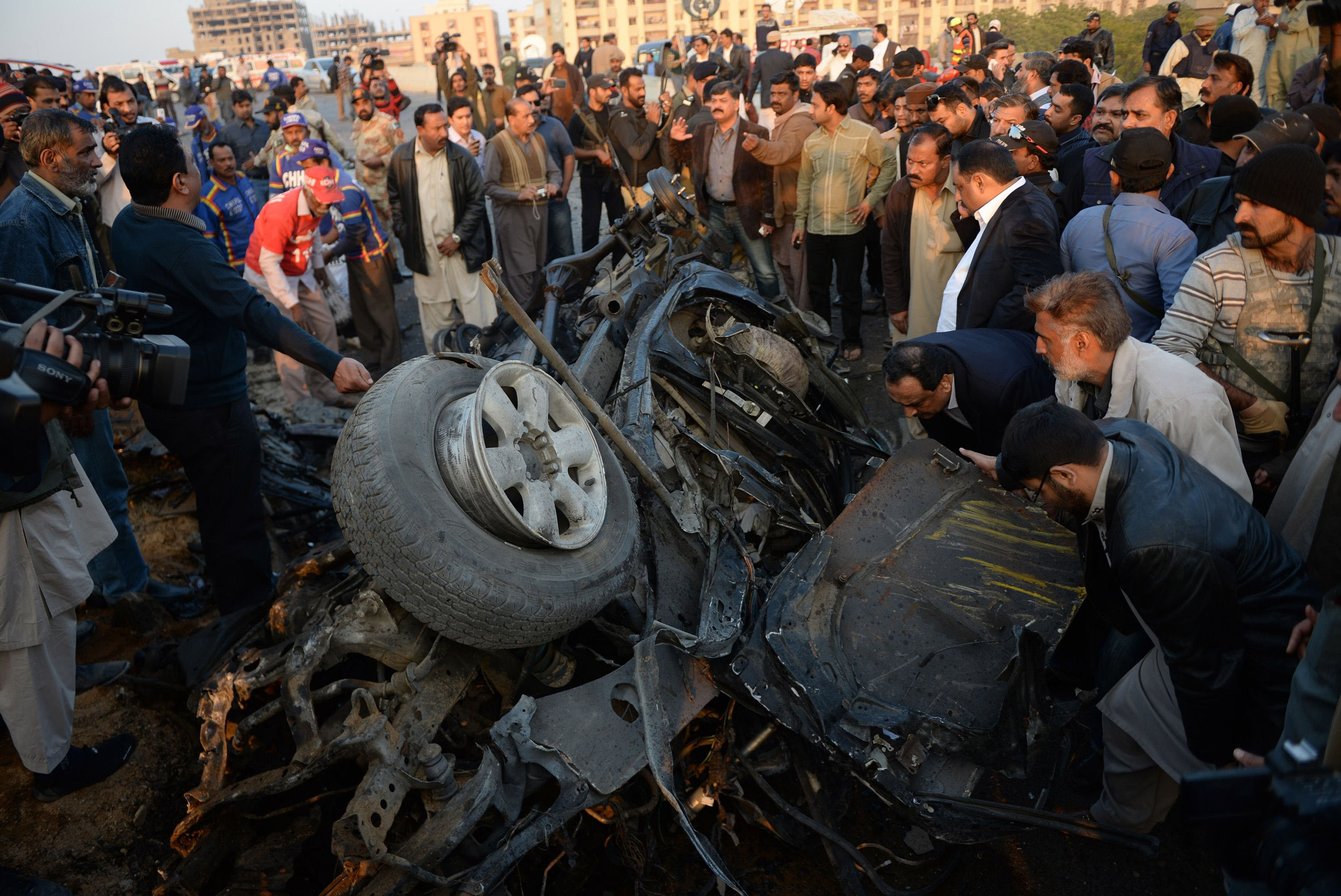 pakistani security officials examine the wreckage of a destroyed vehicle at the site of the suicide bombing in karachi on january 9 2014 photo afp