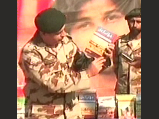 express news screengrab of a frontier corps spokesperson displaying some of the material recovered during the raid
