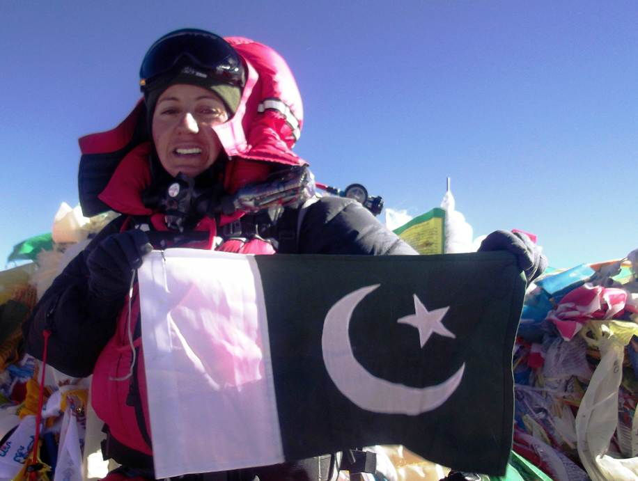 This photograph received from Pakistan Youth Outreach (PYO) and taken on May 19, 2013 shows climber Samina Baig holding  the national flag on the peak of Mount Everest, Nepal.  PHOTO: AFP