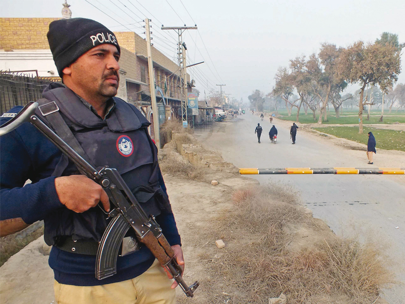 a policeman stands guard near the site of a bomb attack in bannu photo afp