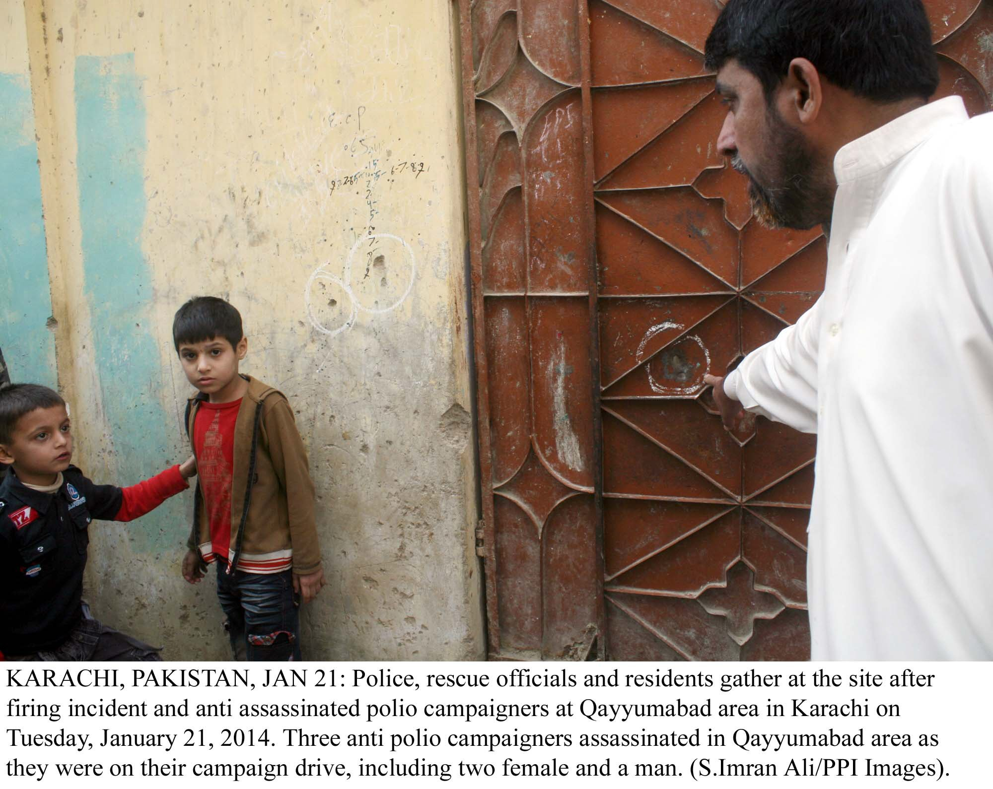 an official points to wards a bullet hole caused by the firing on polio workers in karachi on tuesday as two children look on photo ppi