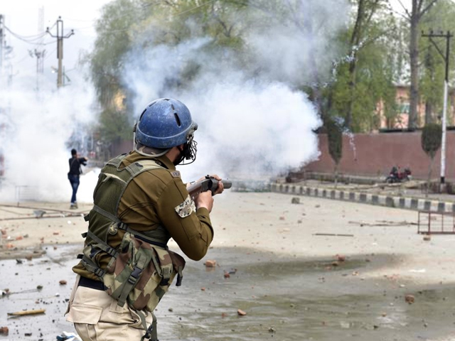 Policeman firing tear gas at protesting Students of Amar Singh Degree College outside their college while protesting after four days of shutdown over the Shopian killing, on April 5, 2018 in Srinagar, India. PHOTO: GETTY