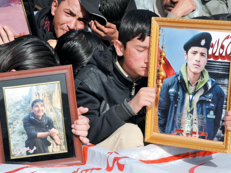 Families hold pictures of their loved ones during the funeral of blast victims. PHOTO: REUTERS