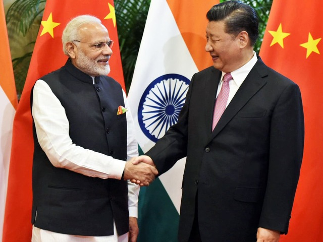Chinese President Xi Jinping shakes hands with Indian Prime Minister Narendra Modi during their visit at East Lake Guest House. PHOTO: AFP