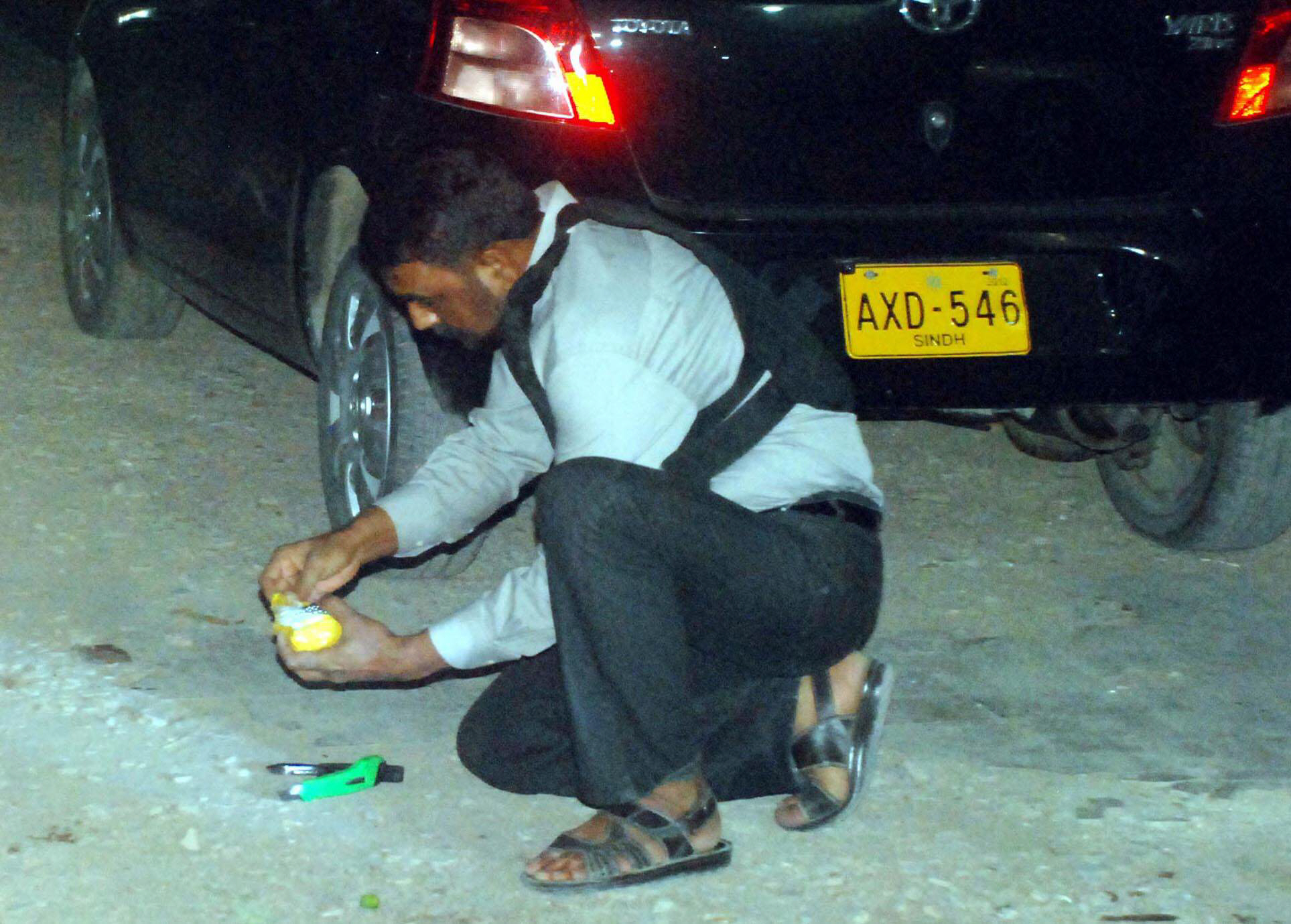 An official of the bomb disposal squad defuses an un-exploded bomb found outside the offices of Nawa-i-Waqt on MA Jinnah road on Monday evening. PHOTO: MOHAMMAD NOMAN/EXPRESS