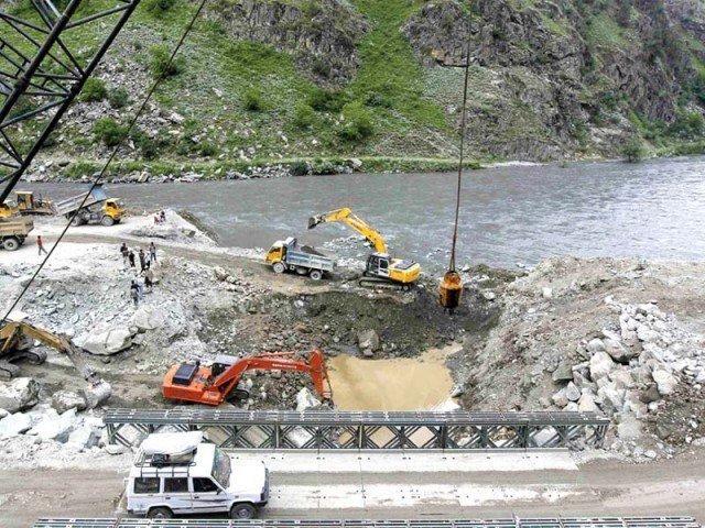 A private vehicle crosses a bridge as excavators are used at the dam site of Kishanganga power project in Gurez, 160 kilometres north of Srinagar. PHOTO: REUTERS
