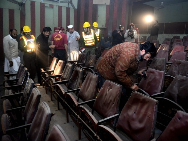 volunteers and security officials investigate the cinema after the attack photo afp file