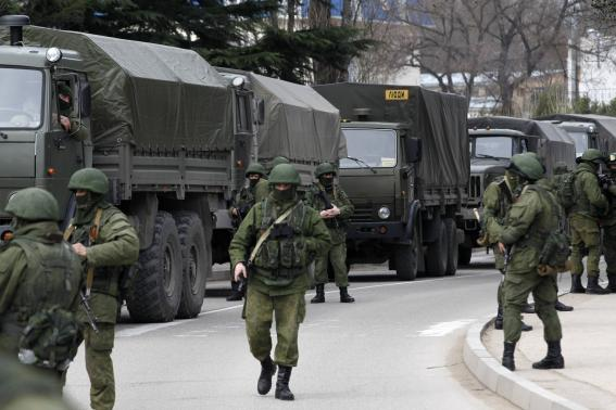 Armed servicemen wait near Russian army vehicles outside a Ukrainian border guard post in the Crimean town of Balaclava March 1, 2014. PHOTO: REUTERS