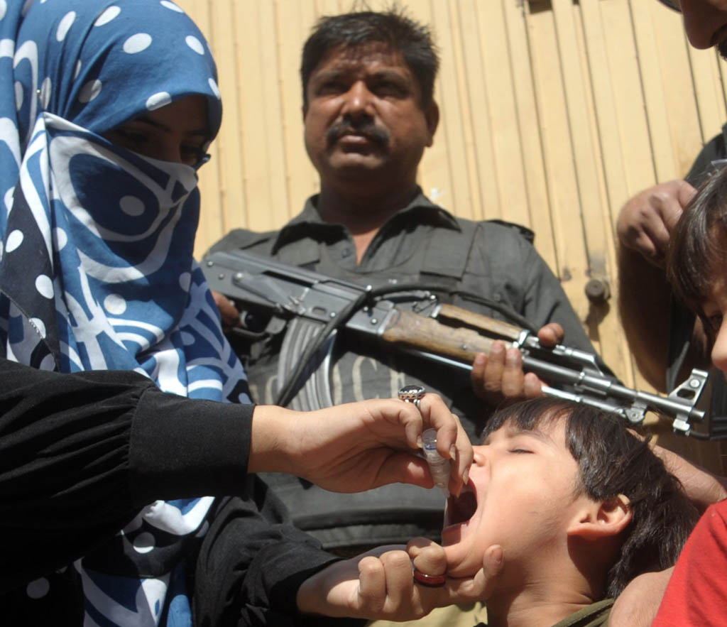 a policeman stands guard as a member of a polio vaccination team administers drops to a child during a door to door vaccination campaign in karachi photo afp